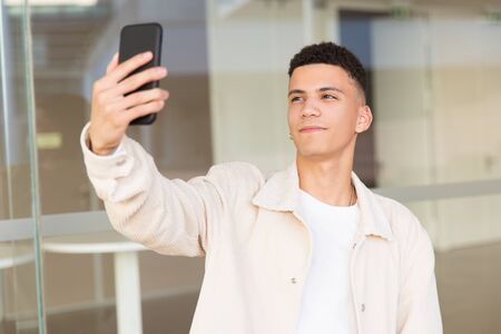 Smiling man taking selfie with smartphone. Portrait of handsome happy young man holding mobile phone and photographing himself. Selfie concept