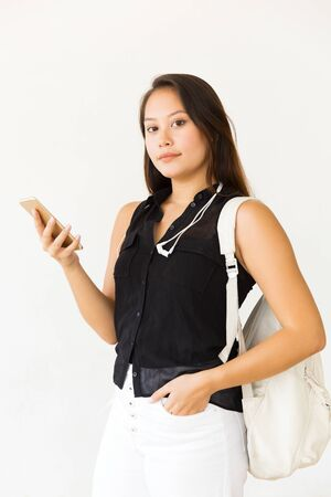 Beautiful young woman using smartphone. Portrait of attractive young female student with backpack holding mobile phone and looking at camera. Technology concept