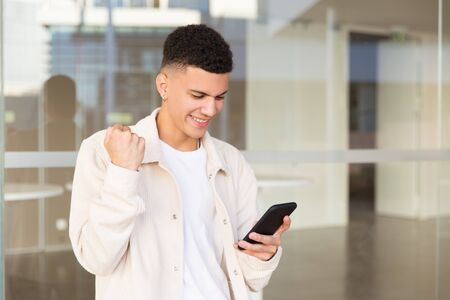 Cheerful young man using smartphone. Happy young man holding cell phone, shaking fist and triumphing near modern building. Emotion and technology concept