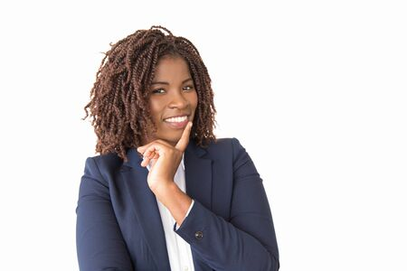 Happy cheerful businesswoman posing in studio. Young African American business lady standing isolated over white background, touching chin, smiling at camera. Business portrait concept