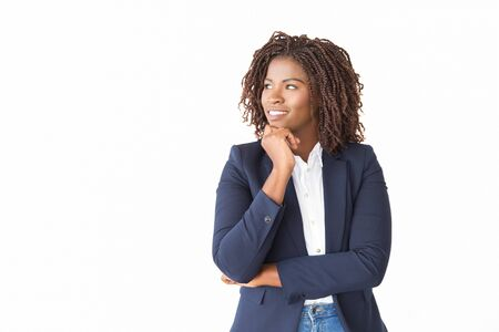 Happy pensive female agent looking at copy space away. Young African American business woman standing isolated over white background, leaning chin on hand, smiling. Advertising concept Stockfoto