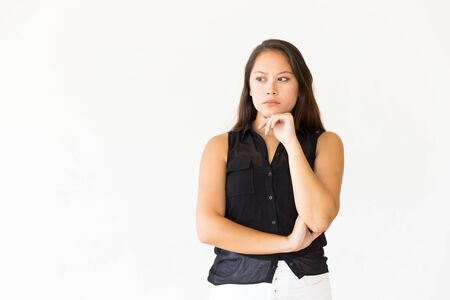 Pensive puzzled female customer leaning chin on hand and looking at copy space. Young Latin woman in casual standing isolated over white background. Promotion concept