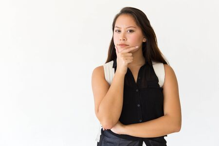 Pensive focused student girl looking at camera. Young Latin woman in casual standing isolated over white background, touching chin. Thinking concept
