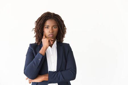 Serious pensive professional posing in studio. Young black business woman wearing formal jacket, standing isolated over white background, touching chin, looking at camera. Business portrait concept