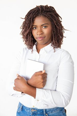 Positive friendly office employee holding tablet, looking at camera. Young African American office worker standing isolated over white background. Digital device for business concept
