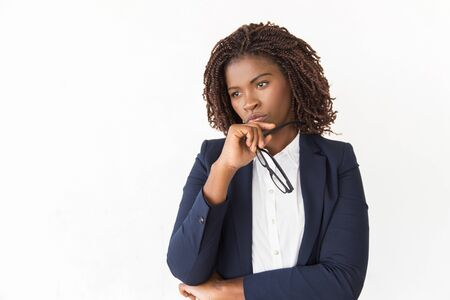 Pensive bored female manager holding glasses, touching chin. Young African American business woman standing Isolated over white background, looking away. Thinking concept