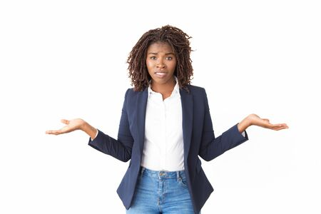 Worried confused female manager making do not know gesture. Young black business woman standing isolated over white, looking at camera, shrugging. Doubt concept