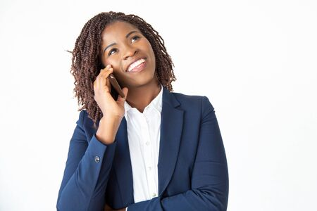 Smiling excited professional talking on mobile phone, looking at copy space. Young African American business woman standing isolated over white background. Communication concept