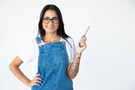 Cheerful brunette in eyeglasses holding pen in raised hand. Studio shot of smiling young woman posing on light background. Idea concept Zdjęcie Seryjne