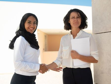 Happy confident business partners posing outside. Muslim businesswoman shaking hands with female colleague. Partnership concept Foto de archivo