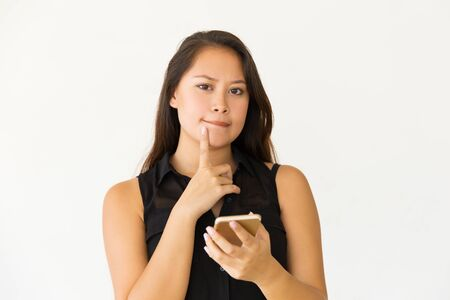 Thoughtful woman with smartphone looking at camera. Portrait of beautiful young brunette woman holding mobile phone and looking at camera. Technology concept