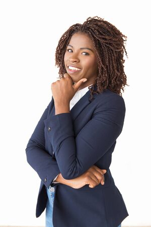 Happy joyful professional touching chin, smiling. Young African American business woman standing isolated over white background, looking at camera. Positive business portrait concept Stockfoto