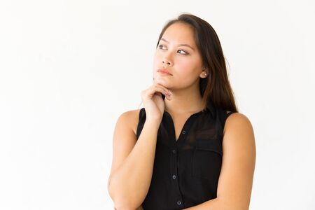 Pensive serious student girl touching chin, looking at copy space. Young Latin woman in casual standing isolated over white background. Thinking over special offer concept