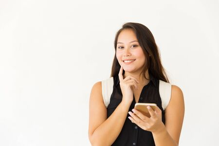 Happy woman with smartphone smiling at camera. Portrait of beautiful smiling young female student with backpack using mobile phone on white background. Technology concept Stockfoto