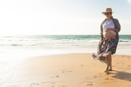Smiling future mother walking on beach during vacation. Happy pregnant woman holding hand on belly. Pregnancy concept 免版税图像