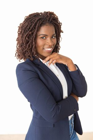 Cheerful young employee touching chin, smiling. African American business woman standing isolated over white background, looking at camera. Young professional concept Stockfoto