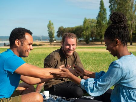 Joyful multiethnic having fun on park lawn. Young man and woman sitting on grass, taking hands of each other, smiling, laughing. Happy friends concept