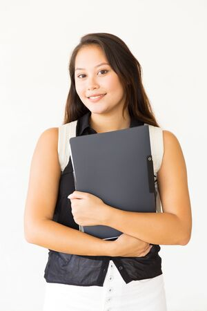 Happy young woman with folder and books. Attractive cheerful young female student with backpack smiling at camera. Education concept