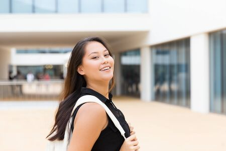 Happy joyful female tourist posing outside. Young mix raced woman in casual standing near city building, adjusting backpack, looking at camera, smiling. Happy young tourist concept 写真素材