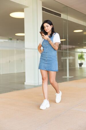 Content young woman using smartphone. Full length view of cheerful stylish young woman using mobile phone and walking in hallway. Technology concept 写真素材