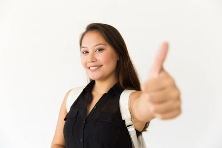 Happy satisfied female customer showing thumb up, making Like gesture. Young Latin woman standing isolated over white background. Positive review concept