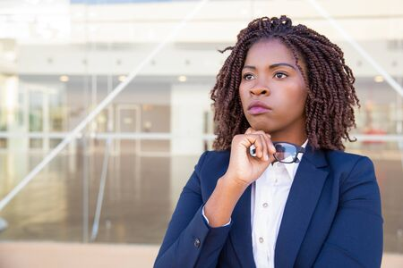 Pensive serious agent waiting customer outside. Young African American business woman standing at outdoor glass wall, touching chin and looking into distance. Outdoor business portrait concept