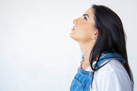 Relaxed attractive brunette looking up. Side view of beautiful young woman on white. Concept of attention