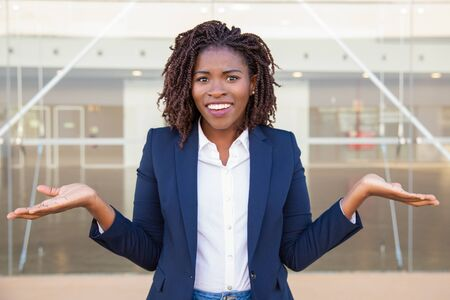 Cheerful confused female manager posing outside. Young black business woman standing near outdoor glass wall, looking at camera, shrugging. Doubt or question concept 스톡 콘텐츠