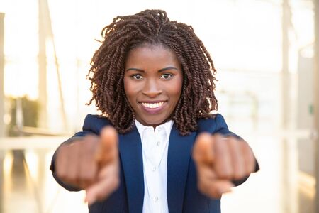 Happy positive recruit agent pointing fingers at camera, choosing you. Young African American business woman standing and posing outside. Career concept