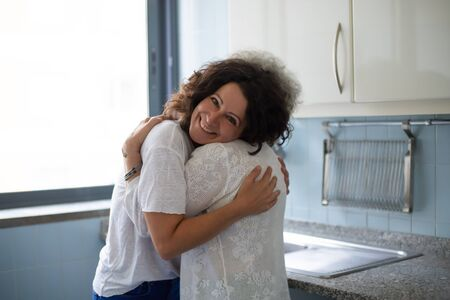 Middle aged woman hugging senior mother in kitchen. Mother and daughter embracing each other at home. Family bonds concept 写真素材