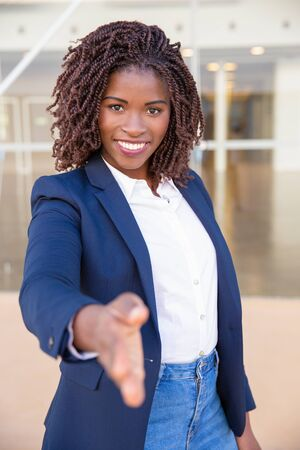 Happy confident business leader introducing at camera. Young African American business woman standing outside, looking at camera, smiling, giving hand for shake. Introduction concept