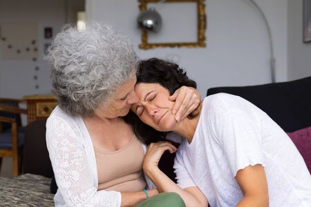 Senior mother giving comfort to upset adult daughter. Elderly lady embracing unhappy middle aged woman in home interior. Mother and daughter bonds concept 写真素材