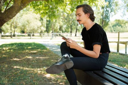 Peaceful serious guy reading on tablet screen outdoors. Young man with curly moustache sitting on park bench, holding and using digital device, looking at screen. Wi-Fi outside concept