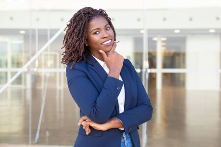 Happy successful leader posing near office building. Young African American business woman standing outside, touching chin, looking at camera, smiling. Confident businesswoman concept