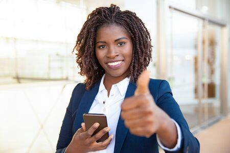 Happy satisfied female customer holding cellphone, making like gesture, showing thumb up. Young African American business woman standing near outdoor glass wall. Positive feedback concept