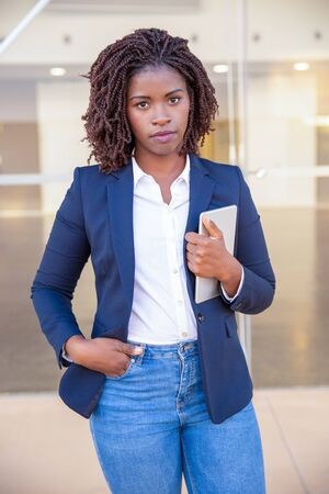 Serious confident agent with tablet posing outside. Young African American business woman standing at glass wall, holding digital device, looking at camera. Successful professional concept 写真素材