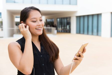 Happy student girl listening to music on cellphone. Young Latin woman wearing earphones, standing outside, holding mobile phone, looking at screen. Video call concept