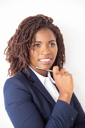 Happy female student holding pen, looking away. Young African American business woman standing isolated over white background. Female business portrait concept