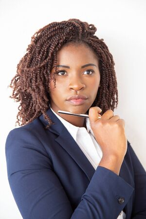 Pensive female student thinking over idea, holding pen, looking away. Young African American business woman standing isolated over white background. Decision making concept