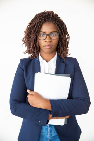 Serious young employee wearing glasses, holding folder and papers. Young African American business woman standing isolated over white background. Office worker with papers concept