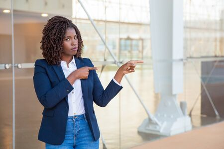 Serious excited customer presenting new product or service. Young black business woman standing at outdoor glass wall, pointing fingers at copy space, looking at camera. Advertising concept