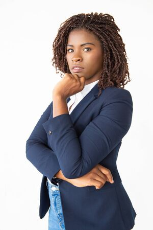 Serious pensive female employee wearing formal jacket, touching chin, looking at camera. Young African American business woman standing isolated over white background. Corporate portrait concept Stockfoto
