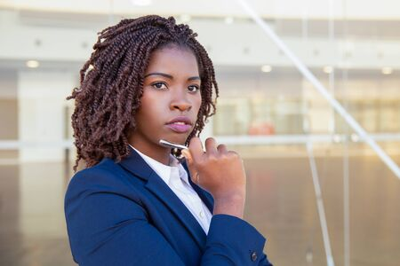 Pensive office secretary posing outside. Young African American business woman standing at glass wall, holding pen, touching chin, looking away into distance. Business portrait concept