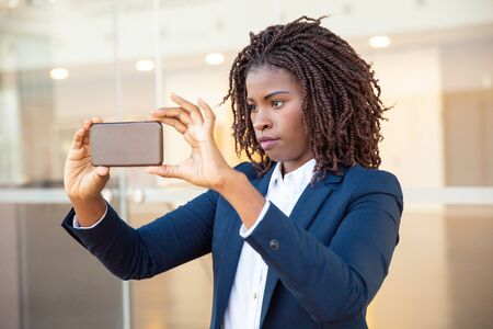 Focused female professional taking picture on cellphone outside. Young African American business woman standing near outdoor glass wall. Photo concept
