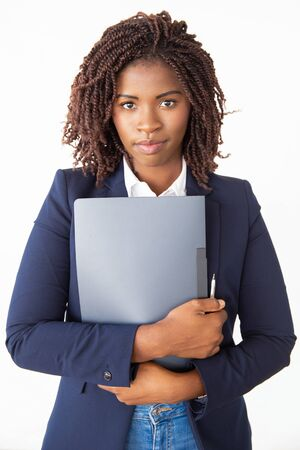 Positive intern holding folder with documents, CV, application, looking at camera. Young African American business woman posing isolated over white background. Career concept