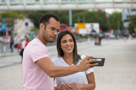 Cheerful couple posing for selfie on street. Happy multiracial friends taking self portrait with smartphone. Concept of self portrait 写真素材