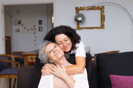Happy peaceful middle aged woman hugging elderly lady in living room. Mother and daughter embracing each other at home. Visit parents concept 写真素材