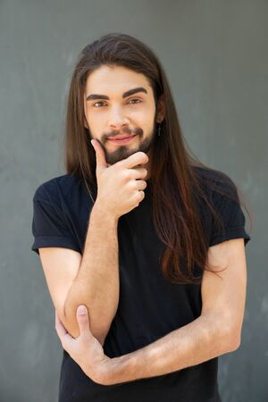Cheerful confident long haired guy posing over grey background. Handsome young man with stubble touching chin, looking at camera and smiling. Front view. Male portrait concept