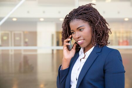 Positive excited office employee talking on cell. Young African American business woman standing outside, speaking on mobile phone, smiling. Communication concept