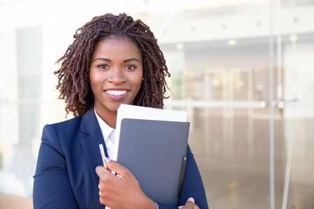 Happy friendly office assistant posing outside. Young black business woman standing at glass wall, holding documents, looking at camera, smiling. Assistant or paperwork concept